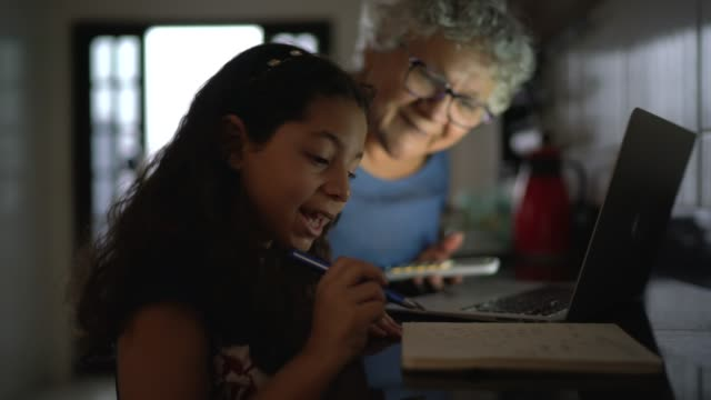 Grandmother and granddaughter using laptop at home
