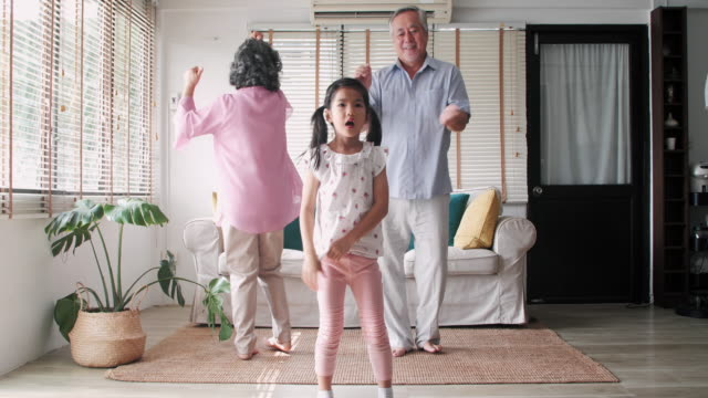 grandmother and grandfather together with their granddaughters dancing in home.leisure, holidays, fun and people concept - happy family dancing at summer party in home. - grandparents stock videos & royalty-free footage