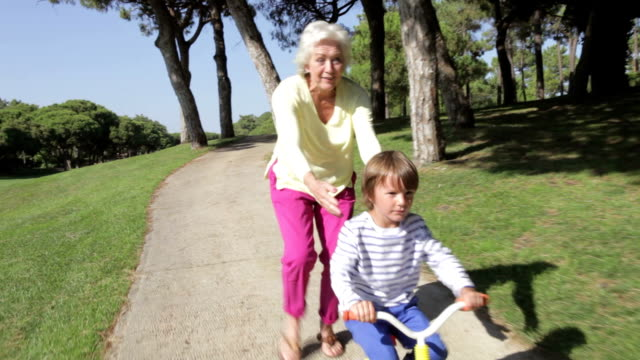 Grandmother And Grandson Riding Bike In Park video