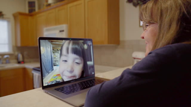 a grandmother and her little granddaughter having fun, talking, laughing on a video chat - video call with family stock videos & royalty-free footage