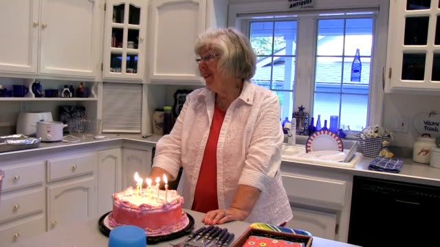 Grandmother blowing out cake candles on her birthday video