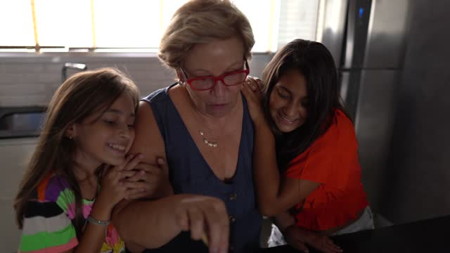 Grandmother cooking with granddaughters at home video