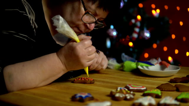 Grandmother covers glaze the gingerbread on the eve of the holiday. video