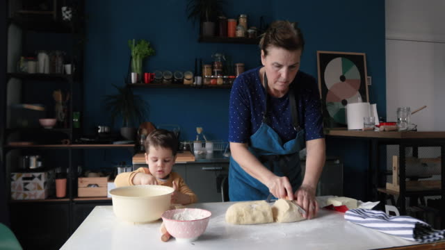 vídeos de stock e filmes b-roll de grandmother cutting dough into small pieces - baking bread at home