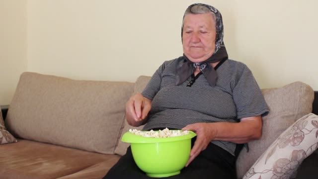 grandmother eating popcorn from the bowl - jungle filmów i materiałów b-roll