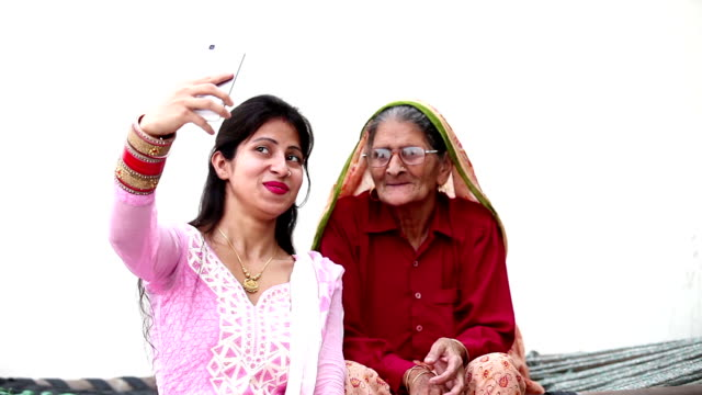 Grandmother & Granddaughter taking  a selfie Old grandmother in traditional dress sitting on a Charpai (Cot) and her Younger granddaughter taking a selfie with him against white background. granddaughter stock videos & royalty-free footage