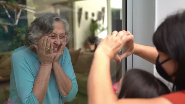 Grandmother greeting daughter and granddaughter through window during quarantine - wearing face mask video