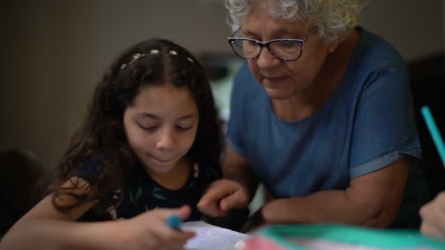 nonna che aiuta la nipote con i compiti mentre studiano a casa - nipote femmina video stock e b–roll