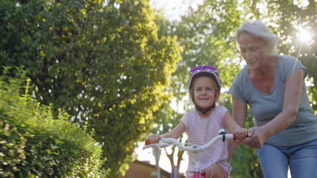 SLO MO DS Grandmother holding the seat of the bike her granddaughter is learning to ride in sunshine Wide slow motion low angle front dolly shot of a senior woman holding the bike her granddaughter is learning to ride in sunshine. Shot in Slovenia. granddaughter stock videos & royalty-free footage