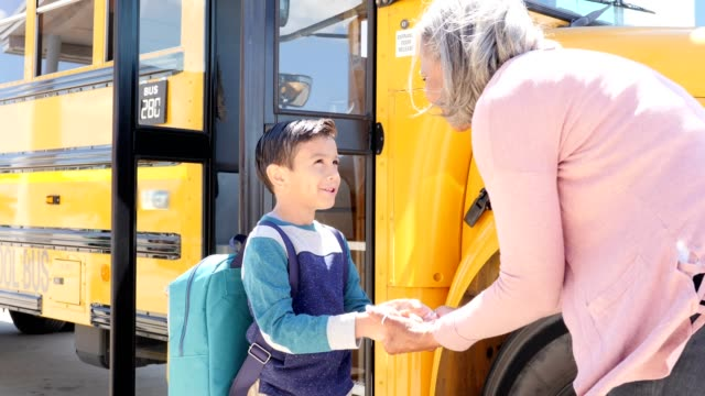 grandmother holds her young grandson's hand as he prepares to board school bus - school buses stock videos and b-roll footage