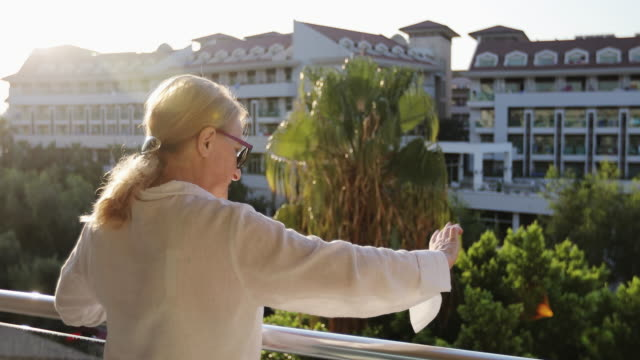 grandmother in sunglasses stands on the balcony and waves. - balcone video stock e b–roll