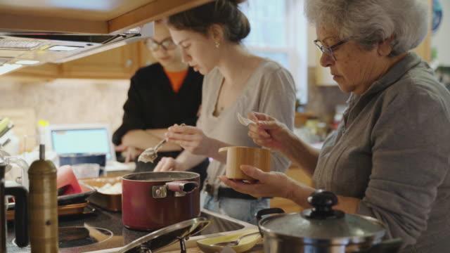 vídeos de stock, filmes e b-roll de vovó está adicionando sal na panela que ela está usando para cozinhar no fogão enquanto sua neta também está cozinhando ao fundo. - jantar