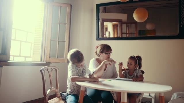 vídeos de stock e filmes b-roll de grandmother is doing homework with children (slow motion) - old men window