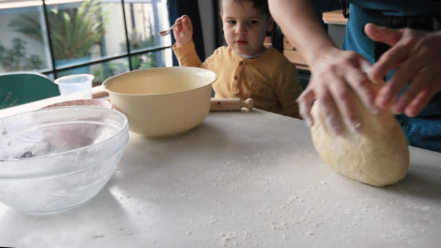 vídeos de stock e filmes b-roll de grandmother kneading yeast dough - baking bread at home