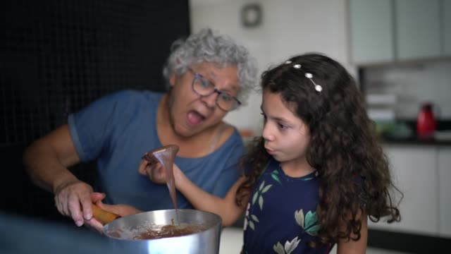 Grandmother making chocolate with granddaughter at home