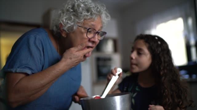 vídeos de stock, filmes e b-roll de avó fazendo chocolate com neta em casa - brigadeiro