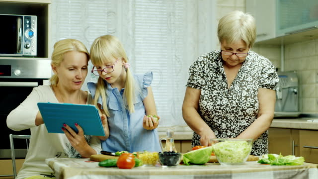 Grandmother, mother and granddaughter cook together a salad in the kitchen. Enjoy a tablet, have a good time video
