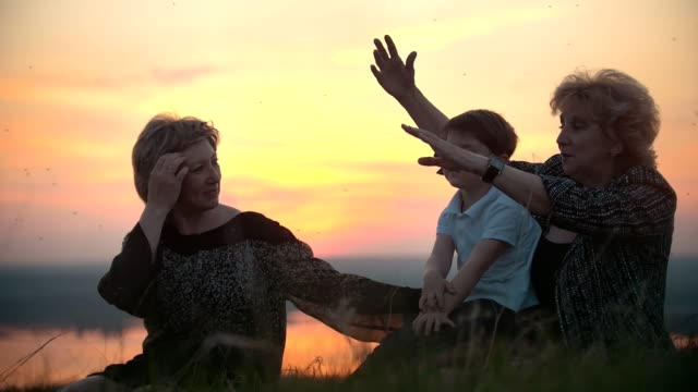 Grandmother, mother with little son on the hill swatting at mosquitoes at sunset video