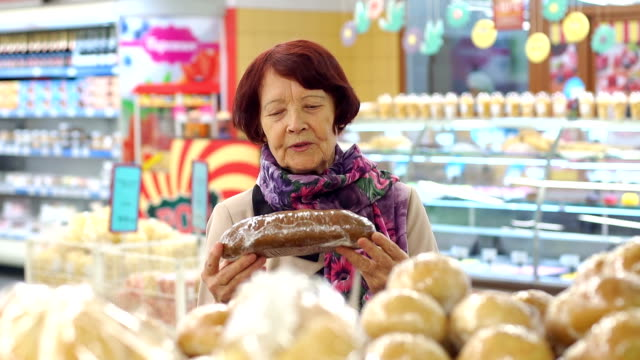 Grandmother of eighty years picks and buys bread at the grocery store. Slow mo.