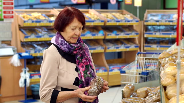 Grandmother of eighty years picks and buys bread at the grocery store.