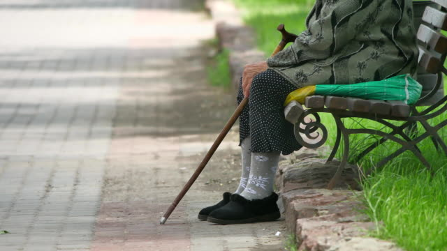 grandmother pensioner homeless poor disabled with crutch sitting on a bench in a park Russia concept poverty outdoors lifestyle - vídeo