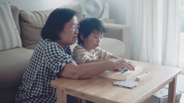 Grandmother playing wood toy with grandchild at home.