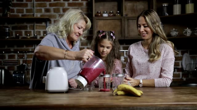 Grandmother pouring berry smoothie into mason jars video