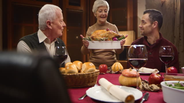 Grandmother presenting the Thanksgiving turkey to her family video