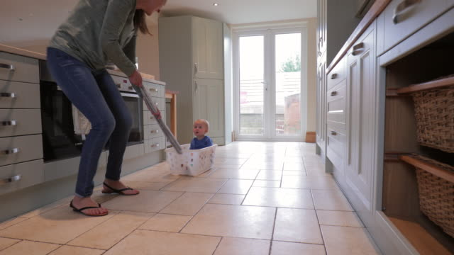 Grandmother Pulling Grandson Across The Kitchen In A Washing Basket Grandmother spends some quality time with her grandson by making the most out of what they have. laundry basket stock videos & royalty-free footage