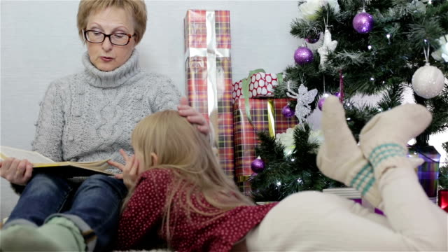 Grandmother reading a book to his granddaughter. video