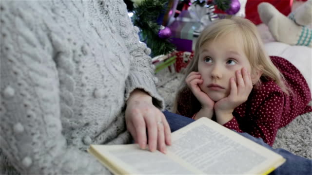Grandmother reading book to his lovely little granddaughter. video