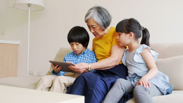 Grandmother Reading to Children in a Home in Taiwan
