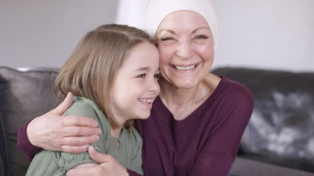 A grandmother recovering from cancer snuggles with her granddaughter on the couch. A grandmother recovering from cancer snuggles with her granddaughter on the couch. They are talking to each other and hugging. affectionate stock videos & royalty-free footage