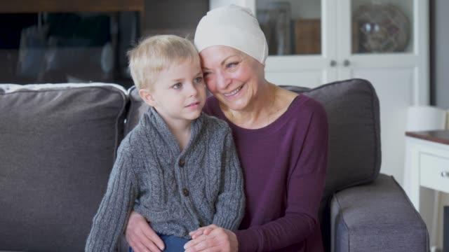 癌から回復している祖母は、彼女の孫をソファーに寄り添っ。 - 回復点の映像素材/bロール