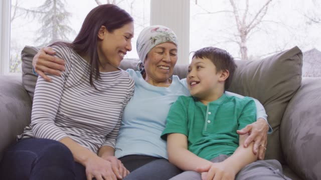 Grandmother Recovering from Cancer with Her Daughter and Grandson A grandmother who is recovering from cancer is sitting with her daughter and grandson on a couch cancer patient stock videos & royalty-free footage