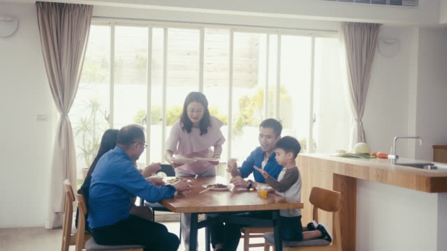 Grandmother serving dinner to multi-generation family