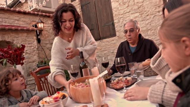 grandmother serving homemade lunch to family in mediterranean village - włochy filmów i materiałów b-roll