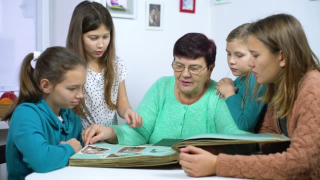 Grandmother showing old photo album to her four granddaughters