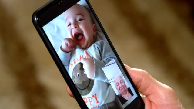 grandmother talks to grandchild on smart phone at home - video call with family video stock e b–roll