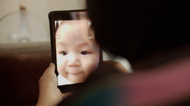 Grand-mère parle à petit-enfant sur la tablette - Vidéo