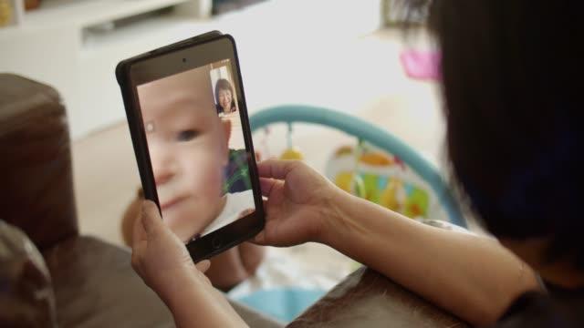 Grandmother talks to grandchild on tablet