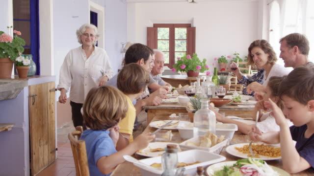 stockvideo's en b-roll-footage met grootmoeder die naar kleinzonen bij lijst loopt - maaltijd