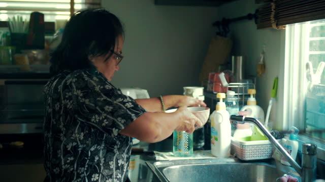 stockvideo's en b-roll-footage met grootmoeder de afwas in de keuken gootsteen thuis - bord serviesgoed
