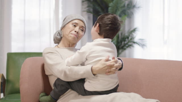 Grandmother With Cancer Playing With Her Grandson An Asian grandmother that has cancer is sitting on the couch and joyfully playing with her young grandson. cancer illness stock videos & royalty-free footage