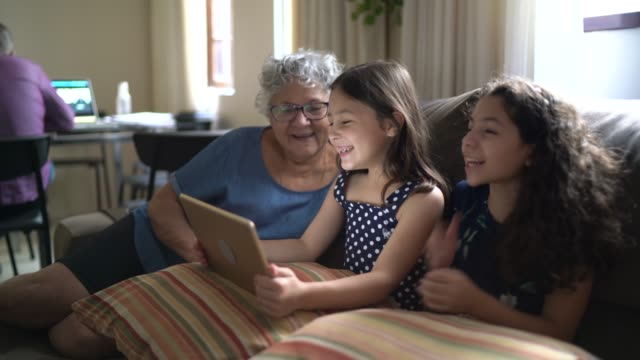 Grandmother with granddaughter using tablet at home Grandmother with granddaughter using tablet at home cousin stock videos & royalty-free footage