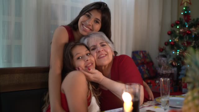 vídeos de stock e filmes b-roll de grandmother with granddaughters portrait at christmas dinner - family christmas