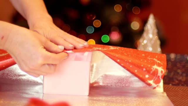 Grandmother wrapping gift for her granddaughter for christmas and new year