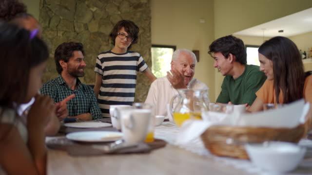 stockvideo's en b-roll-footage met opa verzamelt altijd familie samen - breakfast table