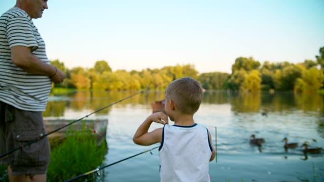 grandpa and grandson fishing - внук стоковые видео и кадры b-roll