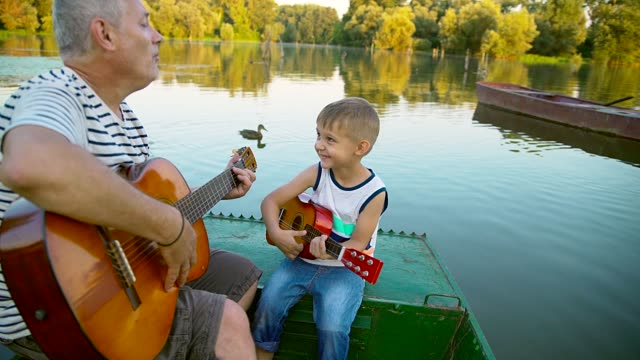 grandpa and grandson play guitar - chitarra video stock e b–roll